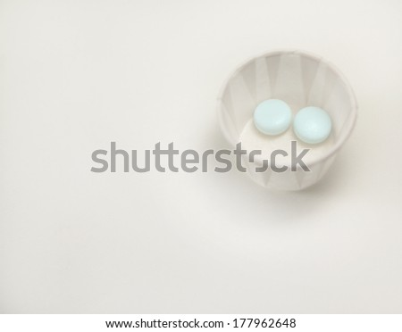 two blue pills in a paper cup
