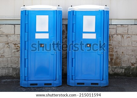 Two blue portable toilet cabins at construction site - stock photo