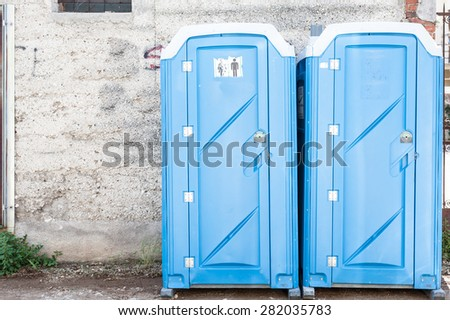 Two Blue Portable Toilet Cabins At Construction Site
