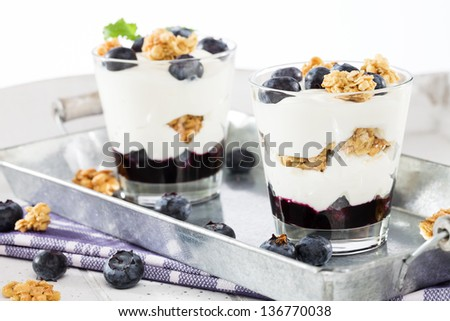 two blueberry yoghurt desserts from side on a metal tray - stock photo