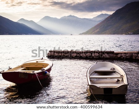 Two boats at the pier in the bay in Montenegro at sunset - stock photo