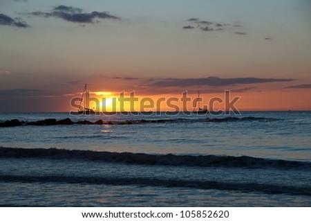 Two boats by orange sunset slow - stock photo