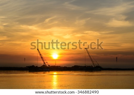 Two boats docking early in the morning near the pier. Horizontal view of a couple of boats loading up cargo in a summer morning over a sun rising sky on background. - stock photo