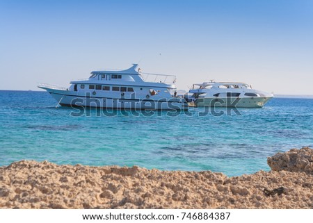 Two boats in red sea crystal clear waters. View from the island.