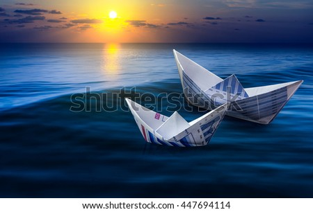 Two boats made from business paper graph on sea with sun light and sky. For business financial ideas concept. - stock photo