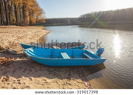 Two boats on the lake, pond. Yellow leaves of the trees. - stock photo