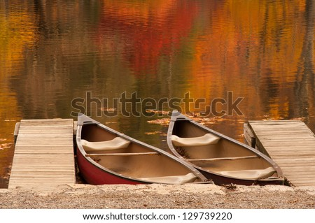 Two boats or canoes sitting in a lake during the peak of autumn in the North Carolina mountains. - stock photo