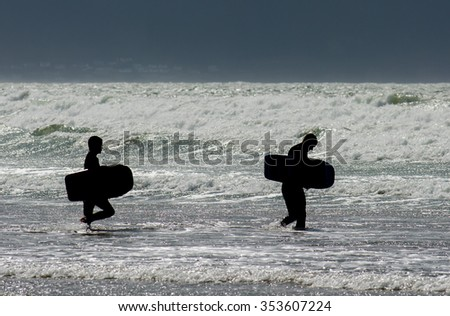 Two Body Boarders Entering Water - stock photo
