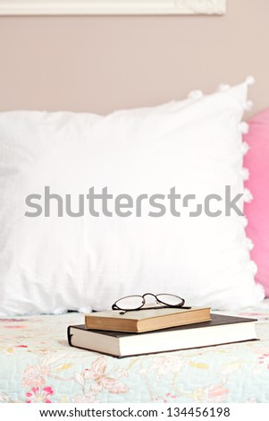 Two books and a pair of glasses laying on top of a bed in a home bedroom. - stock photo