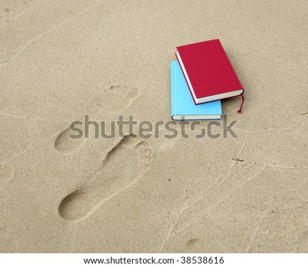 Two books lying beside two footprints. - stock photo