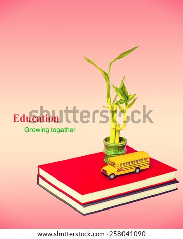 Two books with a model of school bus, bamboo plants. Isolated on pink background. Symbolic concept of Education, school system and children growth. Instagram filtered look. Copy space.  - stock photo
