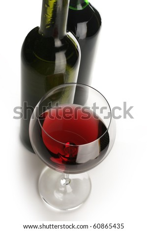 Two bottles and glass of red wine on white background.