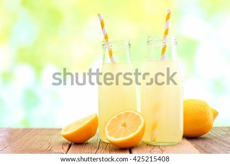 Two bottles of cold lemonade with lemon slices and straws with de-focused outdoor background - stock photo