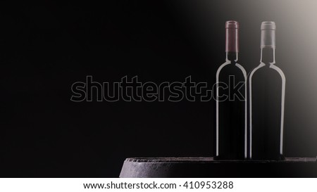 Two bottles of red wine on black background
