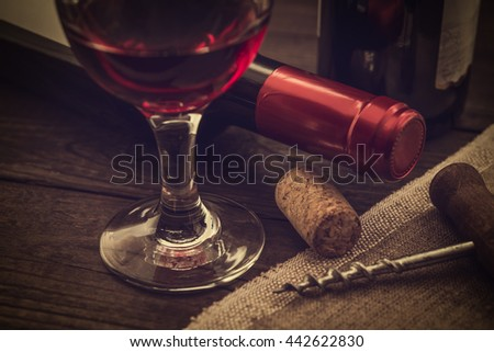 Two bottles of red wine with a glass of red wine and piece of canvas with corkscrew on an old wooden table. Close up view, focus on the glass of red wine, image vignetting and the yellow toning