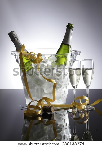 Two bottles of sparkling wine in a cooler with glasses at a celebration. - stock photo