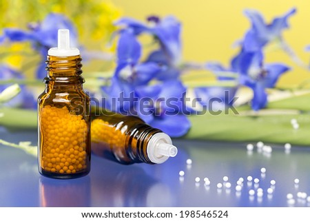 two bottles with homeopathy globules and flowers, with blue reflecting underground. - stock photo