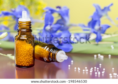 two bottles with homeopathy globules and flowers,with red reflecting underground. - stock photo