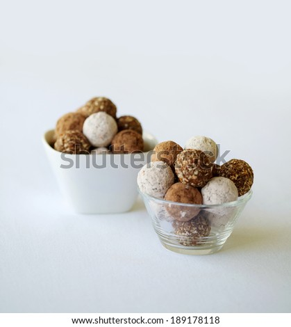 Two bowls of an assortment chocolate balls and rum balls.  This is against a isolated white background. - stock photo