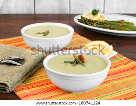 Two bowls of cream of asparagus soup - stock photo