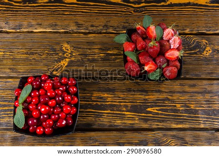 Two bowls of fresh berries, one filled with cherries and the other with succulent strawberries, for a delicious healthy dessert served on an old textured wooden table with copyspace - stock photo
