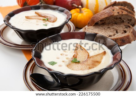 Two bowls of hot delicious Roasted Parsnip and Pear Soup. Garnished with slices of caramelized pears, maple syrup, and parsley. Pumpkins and bread.  - stock photo