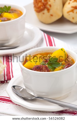Two bowls of hot fresh golden chorizo and chickpea soup and cheese garlic buns - stock photo