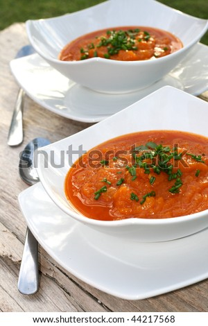 Two bowls of pumpkin soup on wooden table - stock photo
