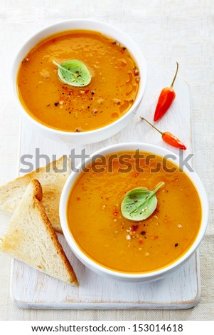 two bowls of squash soup on a white wooden cutting board - stock photo