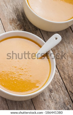 two bowls of squash soup on wooden table  - stock photo