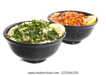 Two bowls with fresh hummus isolated over white - stock photo