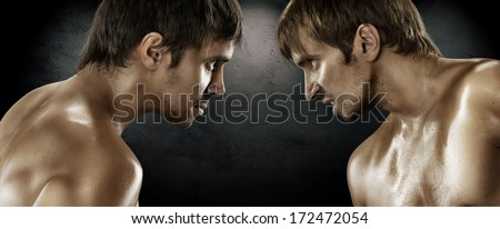 Two boxers facing each other in a match over black background - stock photo