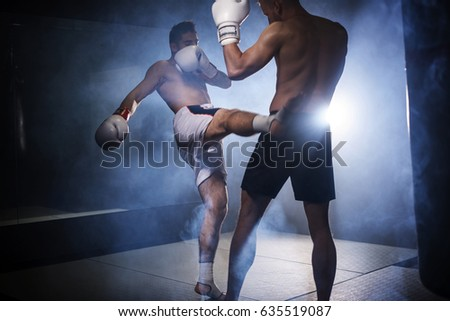 Two boxers training kicks in the gym
