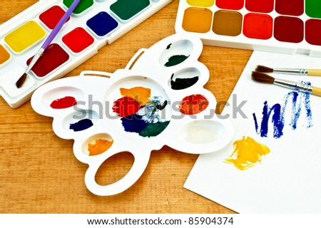 Two boxes of paint, three brushes, white palette in the shape of a butterfly, a piece of paper with a picture on a wooden board