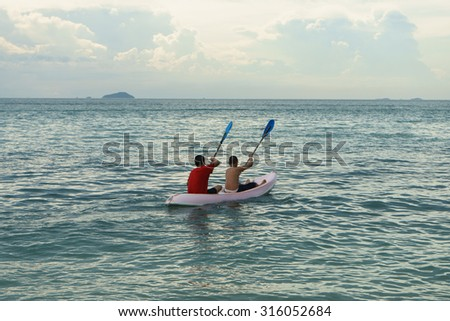Two boy who enjoy kayaking in the ocean - stock photo