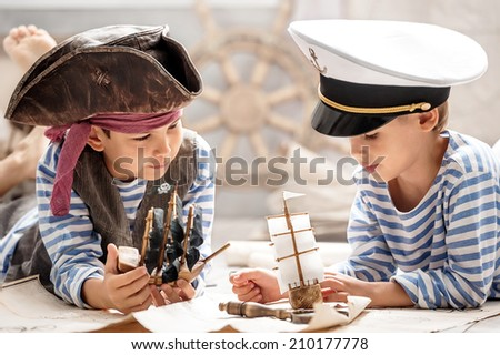 Two boys, a pirate and a sailor, played in a naval battle in his room - stock photo
