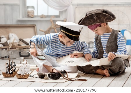 Two boys, a pirate captain, read travel map in her room - stock photo