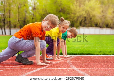 Two boys and girl stand on knee ready to run - stock photo