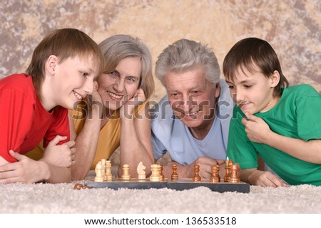 Two boys and their grandparents playing chess on the floor