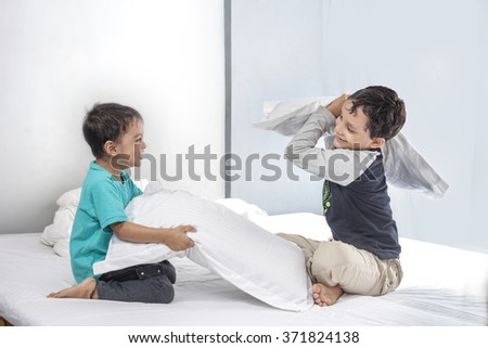 Two boys are fighting there bed room with white pillow