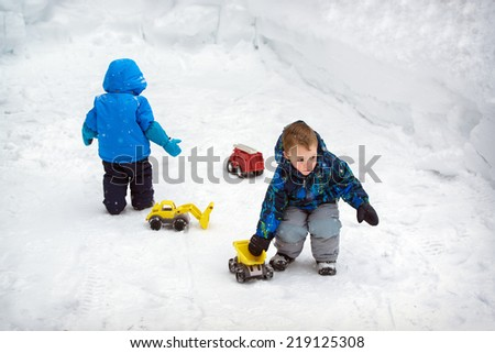 Two boys are playing outside with toy trucks in the snow during a snowfall during the winter season.  There are deep snowbanks around them.  - stock photo