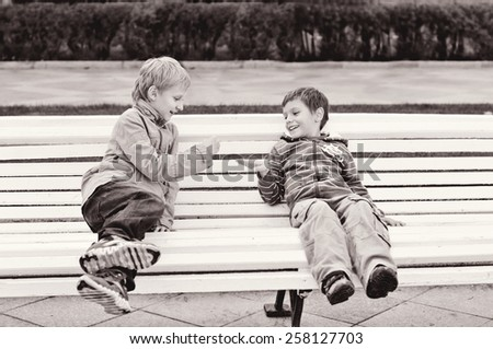 two boys are playing rock-paper-scissor on the bench