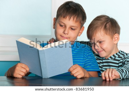 Two boys are sitting at the desk and reading - stock photo
