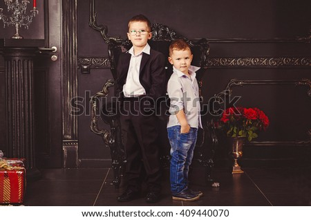 two boys are standing on a black background, the two brothers are on a black background - stock photo