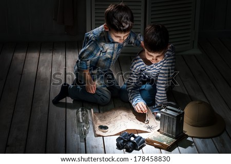 Two boys at night with a flashlight studying an old map in his room - stock photo