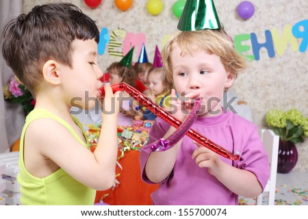 Two boys blow in party blowers at birthday party and three girls fun. Inscription Happy Birthday on wall. Focus on boys. - stock photo