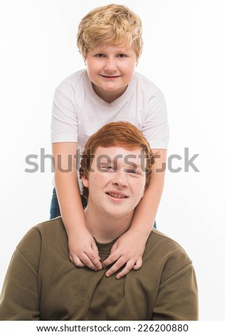 two boys brothers and friends  studio portrait on white background playing  - stock photo