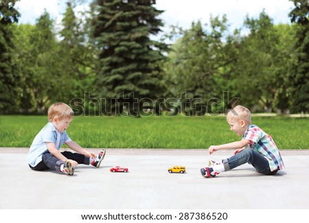 Two boys children playing together with toys outdoors in sunny summer day - stock photo