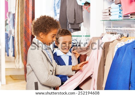 Two boys choose clothes in store while shopping - stock photo