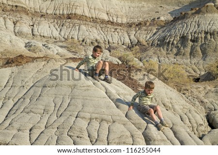 Two boys climb on conglomerate clay bad lands in Dinosaur Provincial Park - stock photo